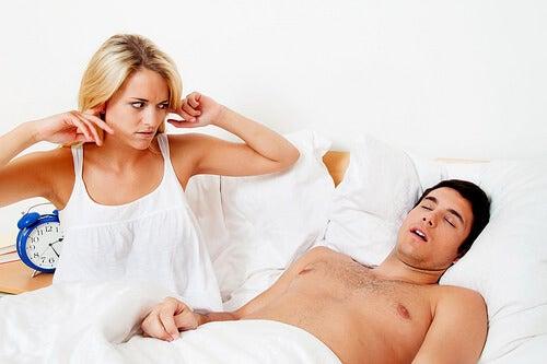 Donna a letto con uomo che russa