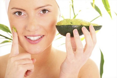 Donna applica una maschera all'avocado sul viso