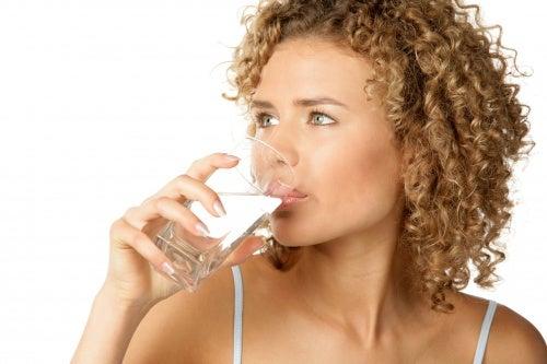 Donna beve bicchiere di acqua