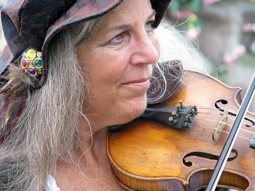 Donna anziana con i capelli bianchi e lunghi e violino