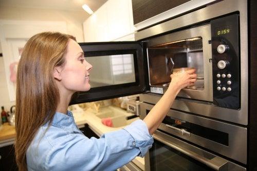 Donna che riscalda acqua nel microonde