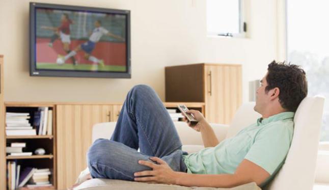 uomo con telecomando davanti alla tv