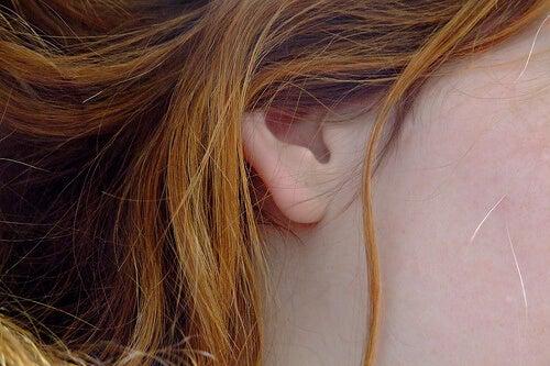 Orecchio di ragazza con capelli rossi