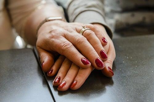 due mani con smalto rosso che si toccano