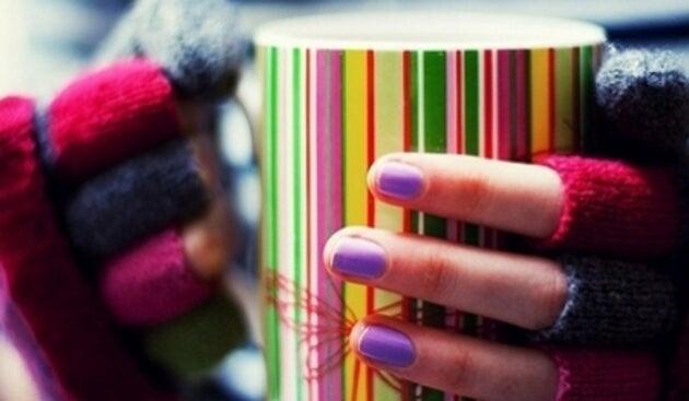 Mani fredde con guanti e tazza colorata
