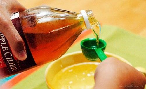 versare aceto di mele in un misurino