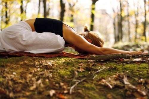 donna che fa yoga nel bosco