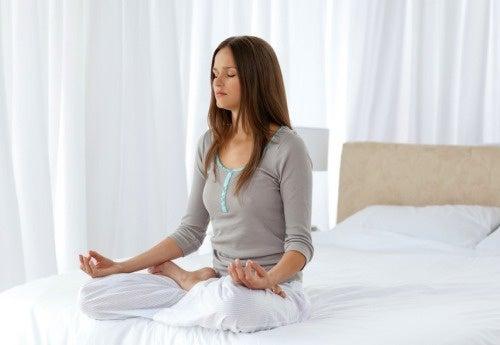 Donna che medita sul letto