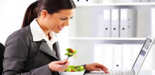 Donna mangia insalata in ufficio