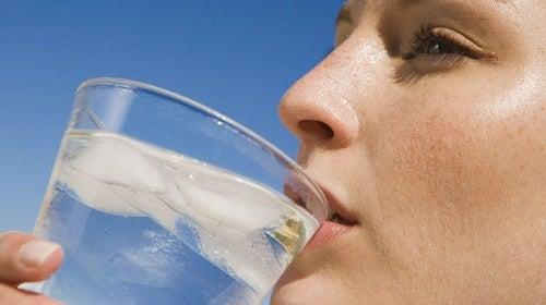 Donna beve un bicchiere di acqua