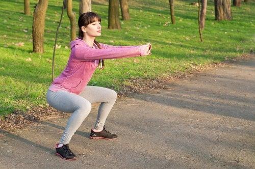 ragazza esegue squat nel parco