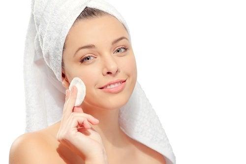 ragazza che pulisce il viso con dischetto di cotone