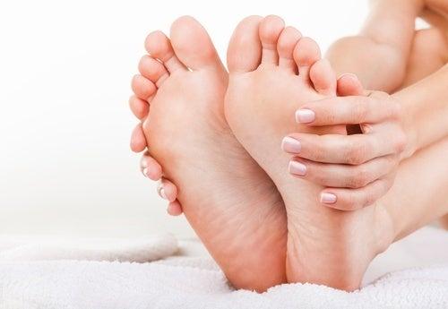Donna con mani sui piedi