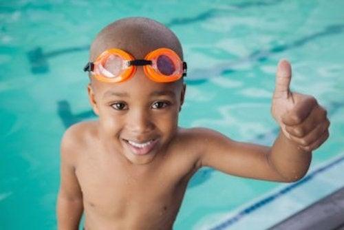 Bambino in piscina con occhialini