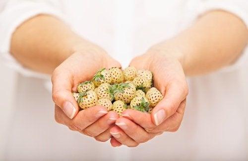 donna con in mano fragole bianche ananasso