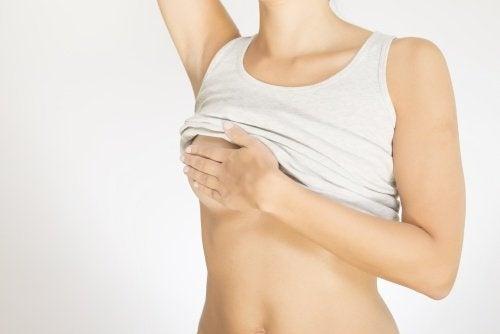 donna che si tocca il seno cancro al seno