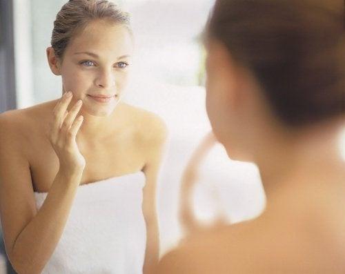 ragazza che si guarda allo specchio cura della pelle