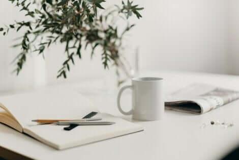 Tazza con penne e quaderno.