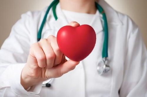 Dottore con cuore di gomma in mano