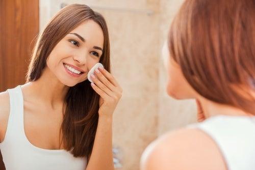 ragazza si deterge il viso davanti allo specchio