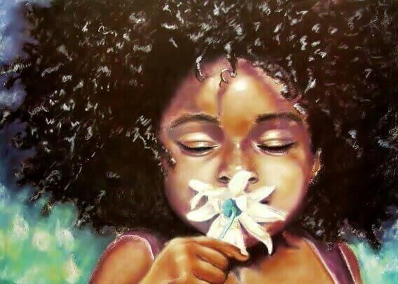 bambina di colore che annusa un fiore