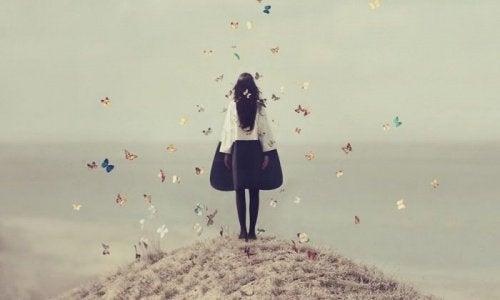 ragazza circondata da farfalle mentre guarda l'infinito