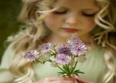 le azioni bambina dai biondi boccoli annusa mazzo di violette