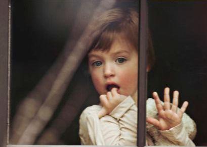Bambina dietro la finestra ipereducazione