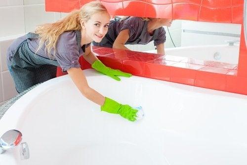 donna pulisce la vasca con aceto bianco