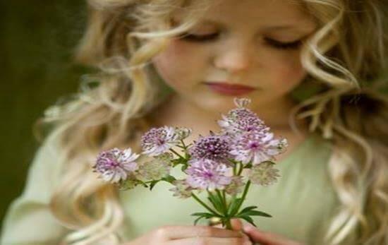bambina bionda con fiori in mano