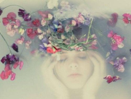 bambina sotto l'acqua con fiori essere forte