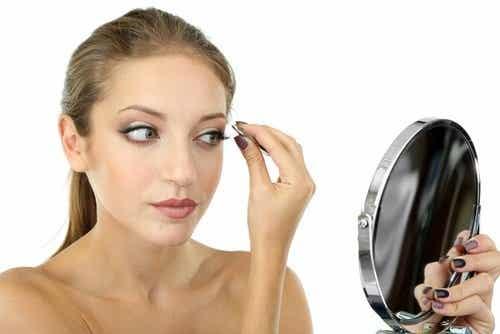 ragazza allo specchio depila le sopracciglia