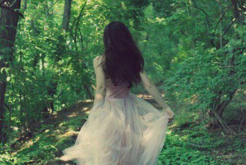 donna di spalle in mezzo al bosco
