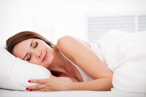 donna dorme con fiori di lavanda sotto cuscino