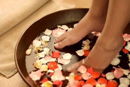 piedi in recipiente con acqua fredda e petali di fiori