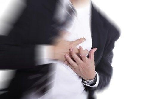 uomo con le mani sul petto palpitazioni