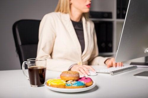donna che lavora e mangia ha emicrania