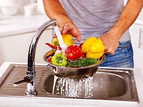 uomo lava la verdura sotto il rubinetto