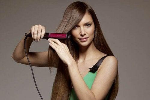 Ragazza che passa la piastra sui capelli
