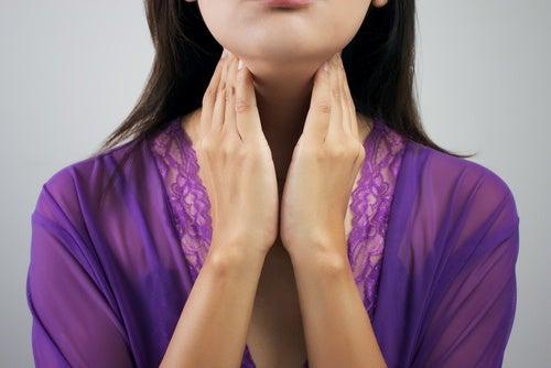 donna con mani sul collo tiroide