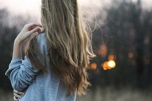 donna di spalle con capelli lunghi vivere