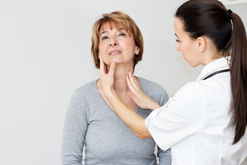 dottoressa tocca la tiroide di una paziente