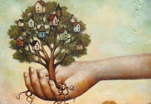 mano con albero con case sui rami fiducia in sé