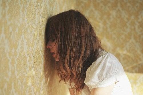ragazza triste con testa appoggiata al muro