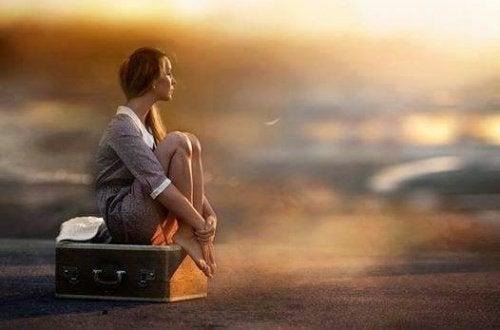 ragazza seduta sopra valigia felici