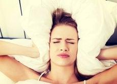 ragazza con cuscino contro le orecchie mal di testa