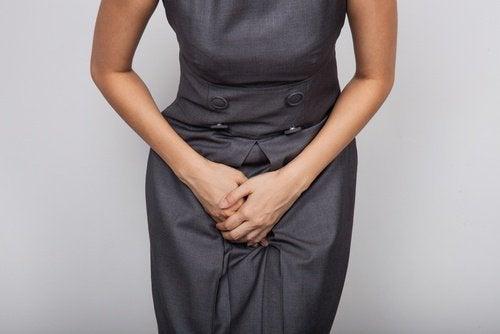 donna mani su vescica per trattenere l'urina