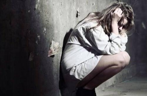 depressione colpisce donna accovacciata sul muro