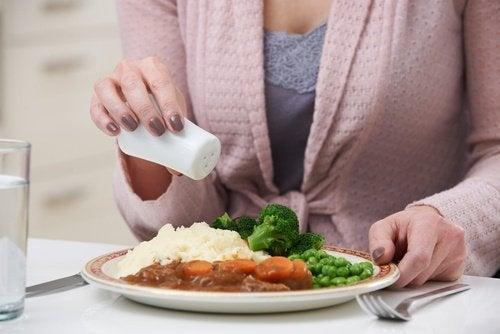 donna che aggiunge del sale ai cibi