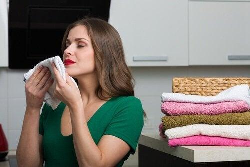 donna che odora un asciugamano ammorbidenti
